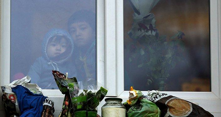 Дети-беженцы смотрят из окна. Архивное фото