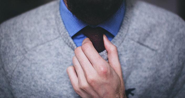 Мужчина повязывает галстук, архивное фото