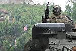Военнослужащий НАТО на бронетранспортере Stryker, архивное фото