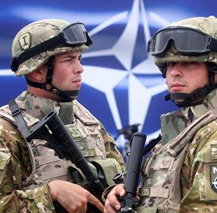 Военнослужащие на фоне эмблемы НАТО, архивное фото