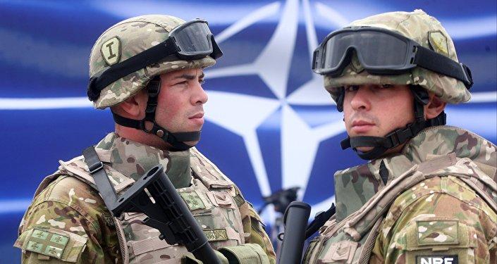 Karavīri NATO emblēmas fonā. Foto no arhīva