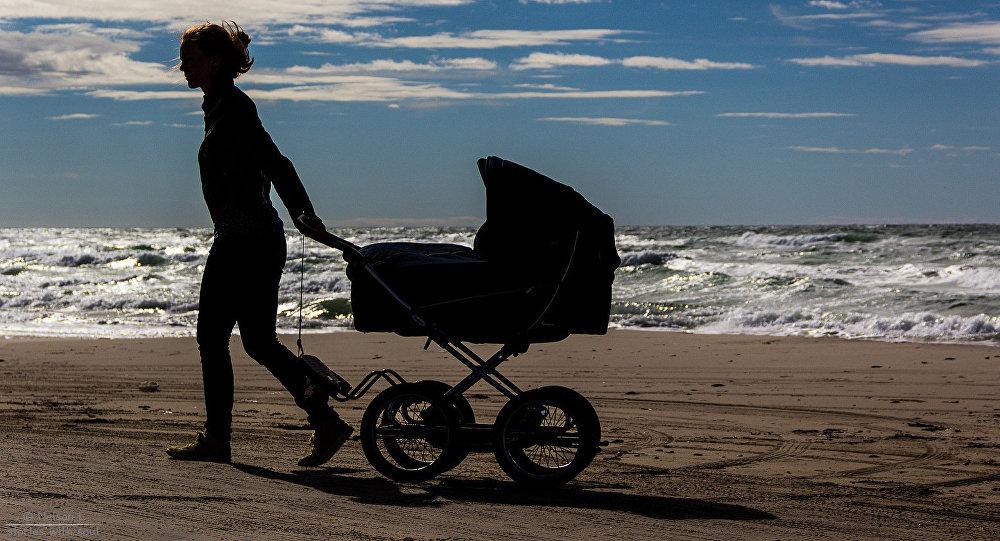 Девушка с детской коляской на берегу моря