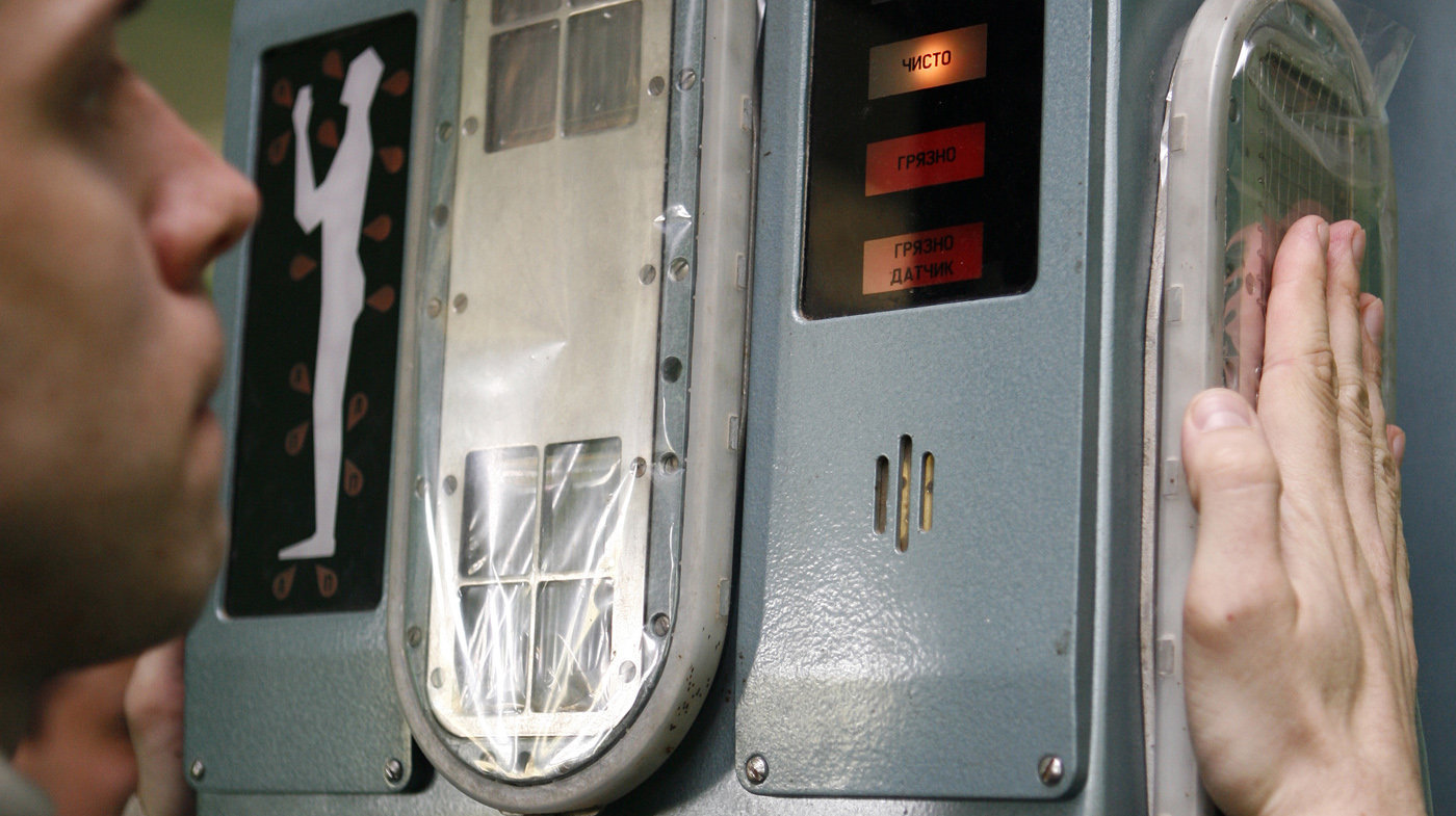 Показано, как надо встать и куда приложить ладони. Если загрязнения нет, загорается зеленая лампочка.