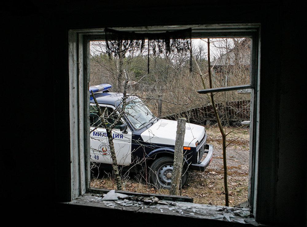 Вид на патрульную машину из брошенного дома в зоне отчуждения ЧАЭС
