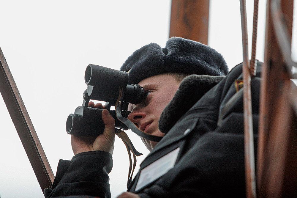 Сотрудник милиции наблюдает в бинокль за обстановкой в зоне