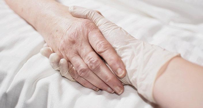 Врач держит за руку больного. Архивное фото