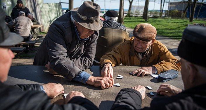 Pensionāri spēlē domino. Foto no arhīva