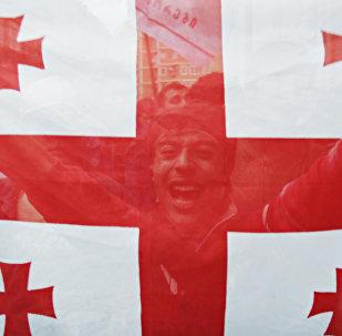 Tbilisi iedzīvotajs ar Gruzijas karogu rokās. Foto no arhīva.