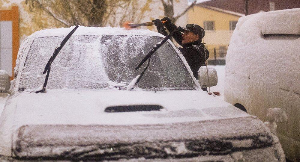 Горожанин чистит автомобиль от снега. Архивное фото