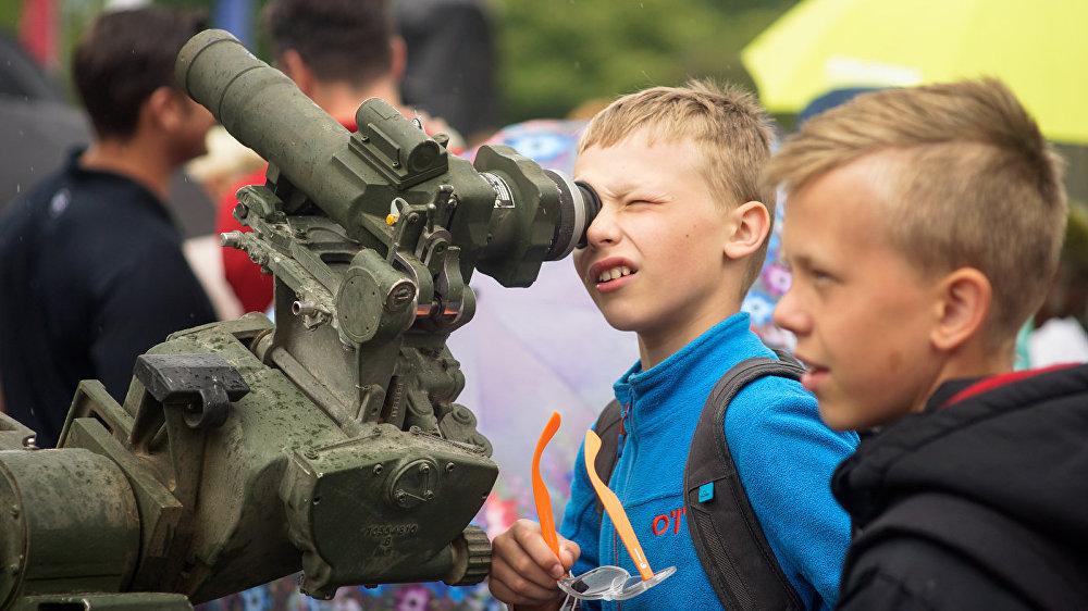 Militārā tehnika izraisīja vietējo zēnu interesi.