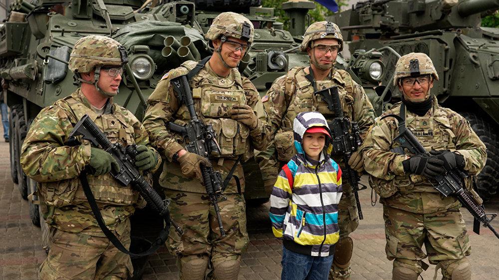 NATO karavīri, draudzīgi smaidot, pozēja pie draudīgās tehnikas.