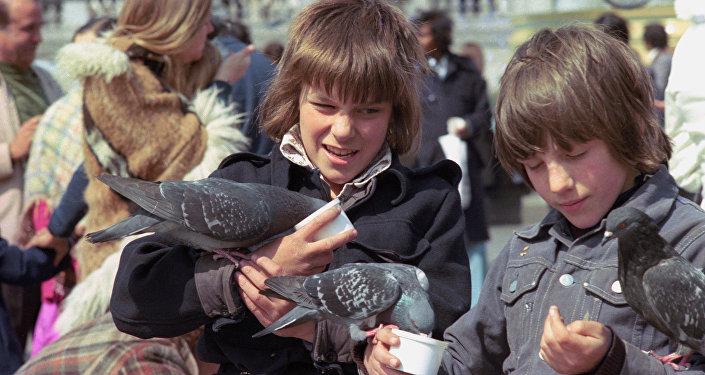 Мальчики с голубями на Трафальгар-сквер в Лондоне. Архивное фото