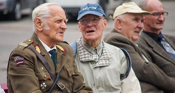 Ветеран в форме латвийской армии беседует с участником мероприятия