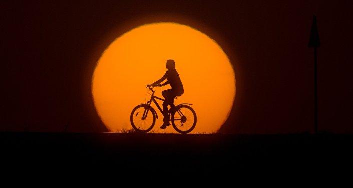 Девушка катается на велосипеде на закате. Архивное фото