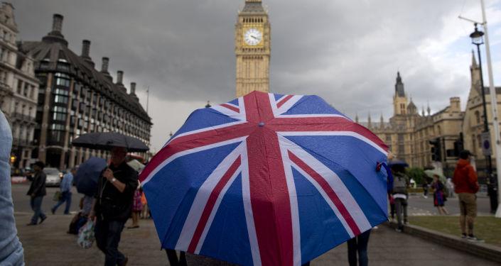 Пешеход с зонтом в цветах британского флага в Лондоне