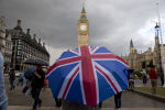 Пешеход с зонтом в цветах британского флага в Лондоне, архивное фото
