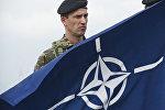 Военнослужащий с флагом НАТО, архивное фото