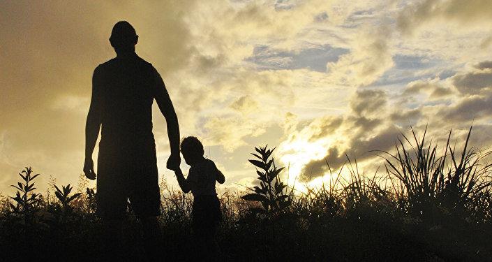 Pieaugušais un bērns saules rietā. Foto no arhīva