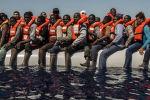 Беженцы ждут спасательную шлюпку в Средиземном море, архивное фото