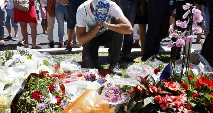 Vīrietis sēro pie terorakta upuru piemiņas vietas Nicā. Foto no arhīva