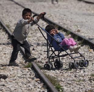 Мальчик везет коляску с ребенком в лагере беженцев в Идомени, Греция