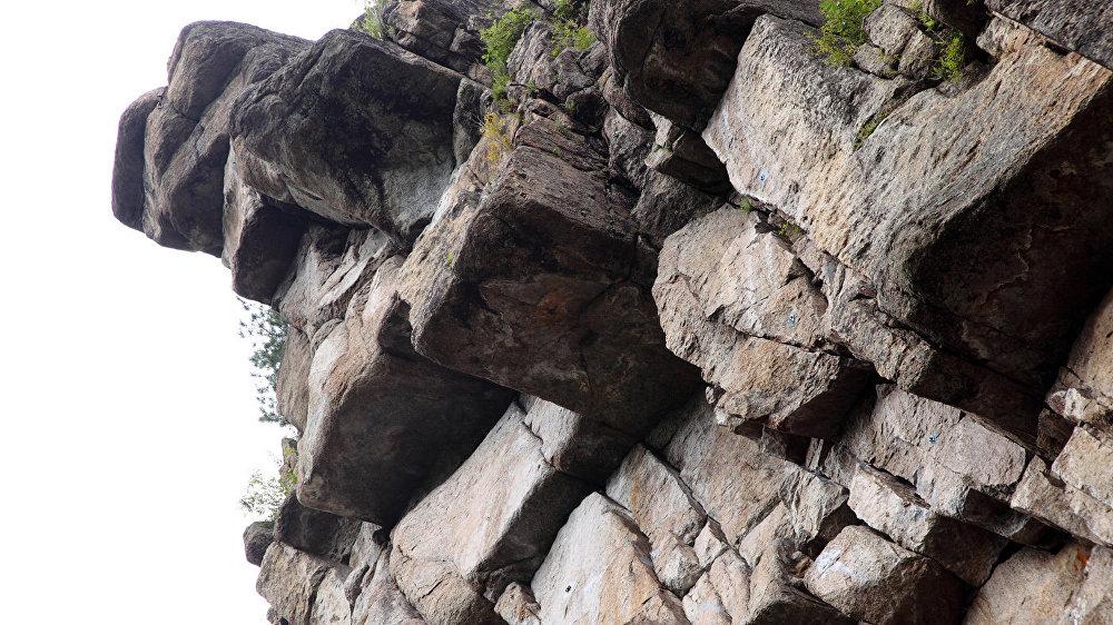 Karavīra klints – skats no lejpuses. Šeit pa negatīvo slīpumu labrāt rāpjas augšup alpīnisti