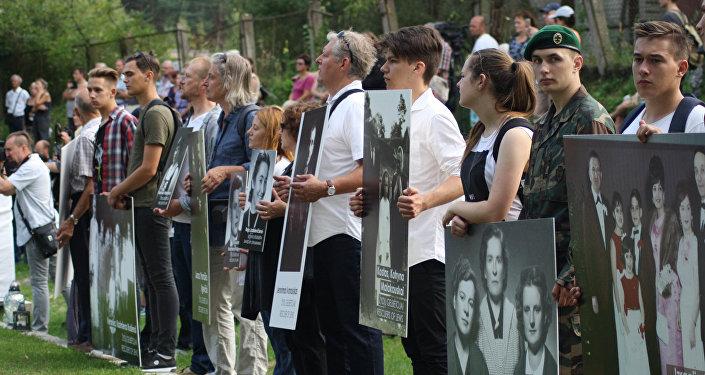 Фотографии в руках потомков на месте расстрела евреев в Молетай