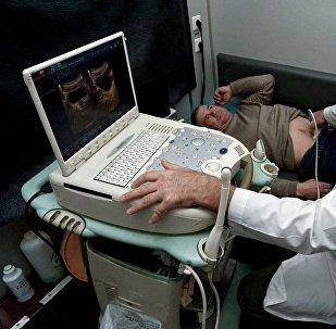 Врач проводит ультразвуковое исследование в кабинете УЗИ, архивное фото