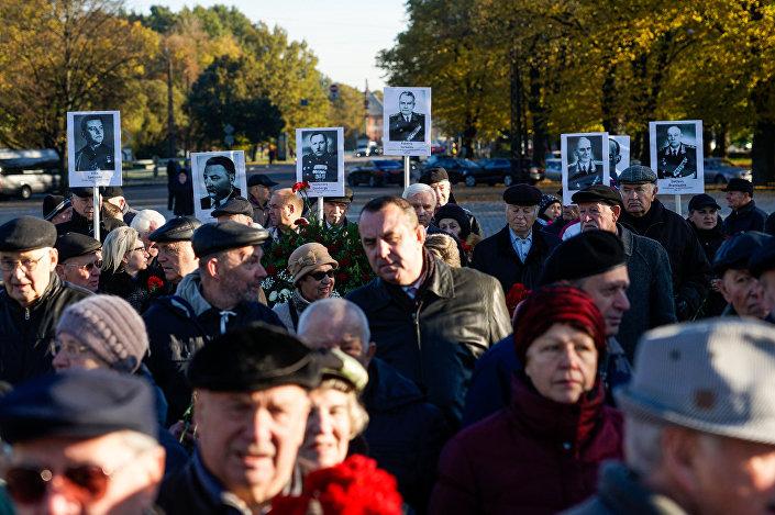 К мемориалу люди пришли с портретами родственников - участников войны
