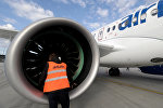 Специалист осматривает самолет Bombardier CS300 в Рижском аэропорту