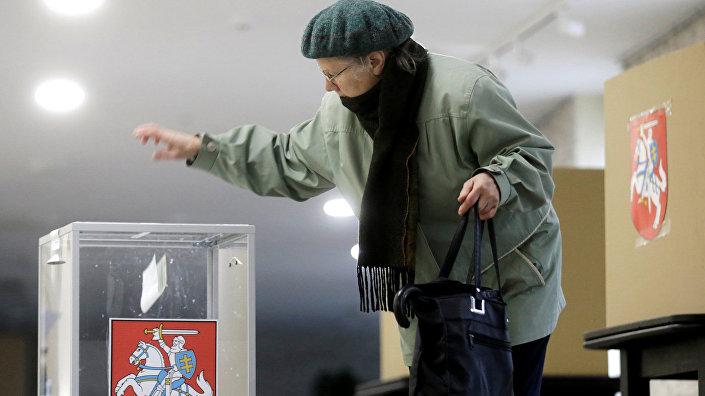 Женщина опускает бюллетень в урну для голосования в Биржае, Литва