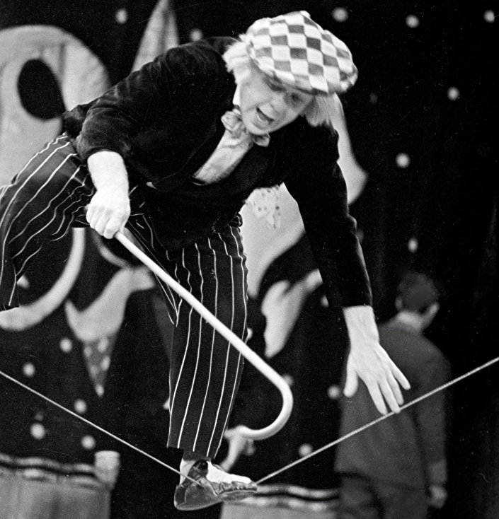 Олег Попов идет по натянутому канату во время выступления на арене цирка