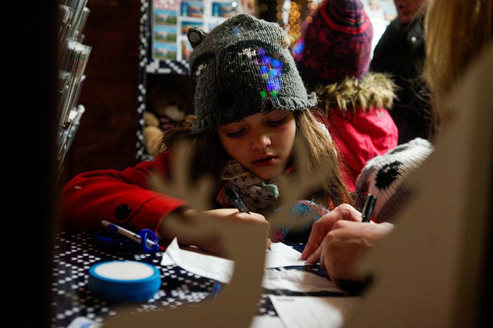 Девочка пишет письмо Санта Клаусу
