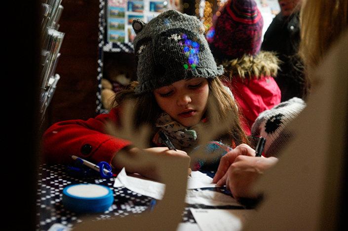 Девочка пишет письмо Санта-Клаусу