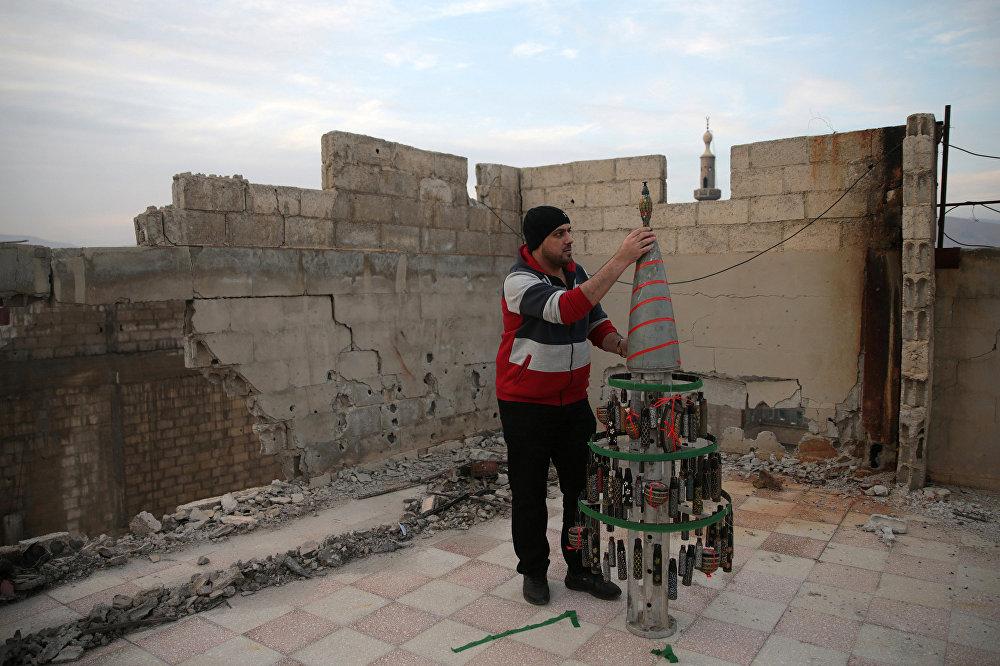 Мужчина делает ёлку из пустых гильз, которые он разрисовал во время осады города Дума в Сирии