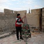 Vīrietis veido eglīti no lādiņu čaulītēm, ko viņš apgleznojis Dumas pilsētas aplenkuma laikā Sīrijā