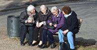 Пожилые женщина на сидят скамейке, архивное фото