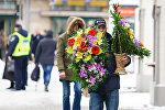 Мужчина несёт корзины с цветами