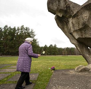 Sieviete noliek ziedus pie figūras Nesalauztais Salaspils Memoriālajā kompleksā