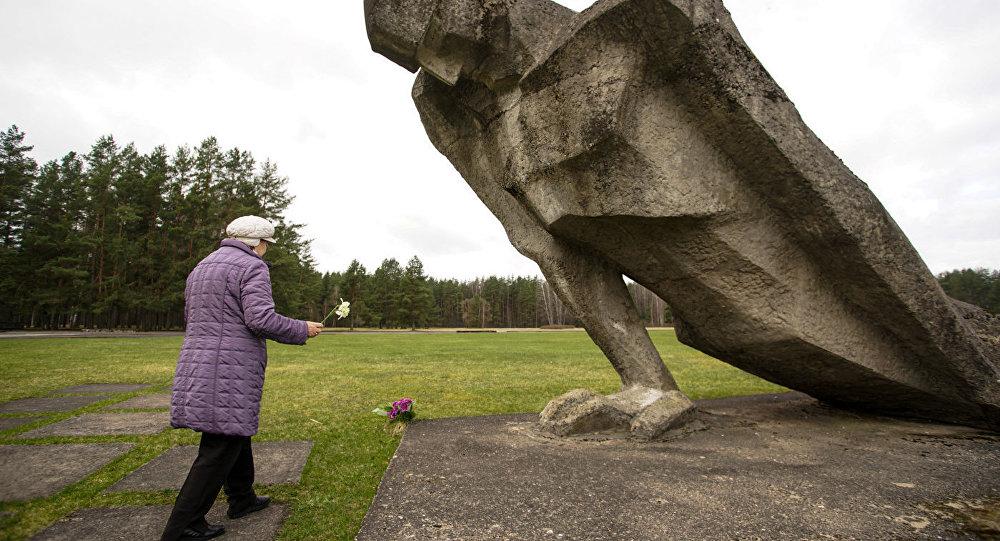 Женщина возлагает цветы к фигуре Несломленный в Мемориальном комплексе Саласпилс