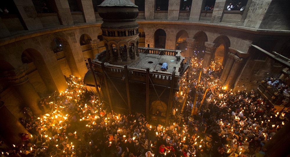Православные верующие держат свечи во время церемонии в Храме Гроба Господня в Иерусалиме