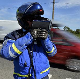 Сотрудник полиции замеряет скорость машин