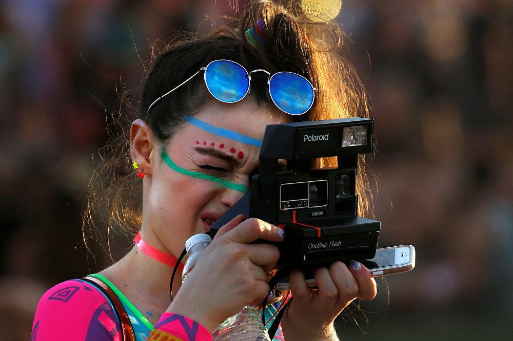 Девушка фотографирует на камеру Полароида на Коачелла-фест