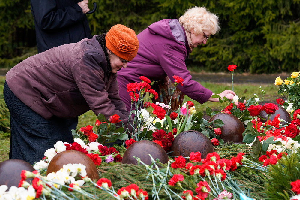 Женщины возлагают цветы в память о советских войнах, погибших во Второй мировой войне на территории Латвии