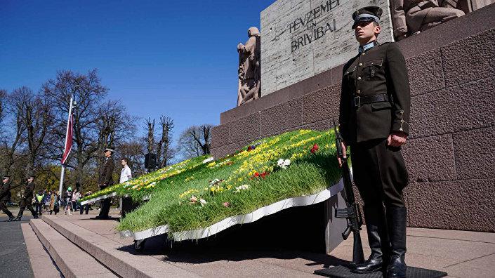 Почетный караул у цветочной композиция у Памятника Свободы