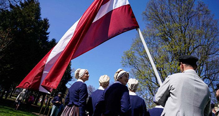 Latviešu tautas kostīmos tērpti mākslinieki ar valsts karogu