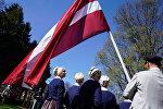 Флаг Латвии у латвийцев в национальных латышских костюмах