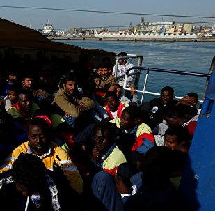 Мигранты ждут прибытия на корабле Феникс в Катанию на острове Сицилия, Италия
