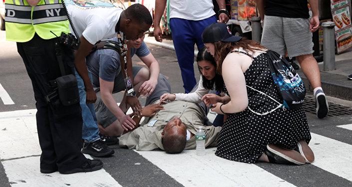 Пострадавший мужчина на тротуаре после наезда автомобиля на толпу пешеходов на Таймс-сквер в Нью-Йорке 18 мая 2017 года
