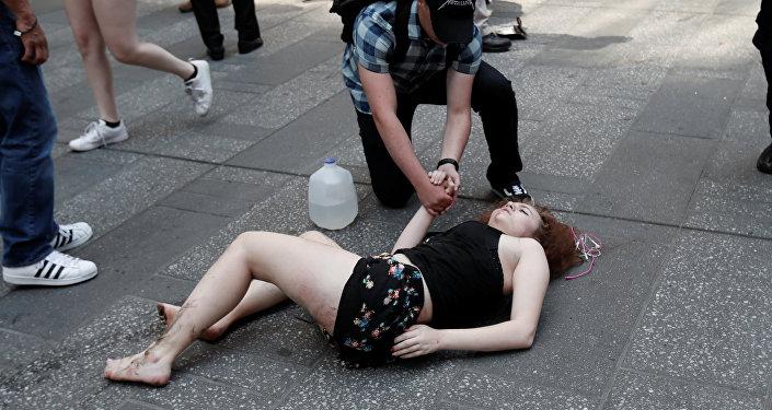 Раненая женщина на тротуаре после наезда автомобиля на толпу пешеходов на Таймс-сквер в Нью-Йорке 18 мая 2017 года